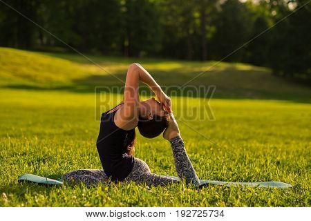 Young woman practicing yoga concept, sitting in One Legged King Pigeon exercise, Eka Pada Rajakapotasana pose, on green suuny field in park. Side view