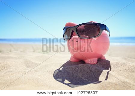 Piggy bank with sunglasses on the beach at the seaside