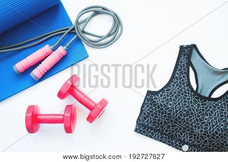 Flat lay of sport bra and sport equipments on white background Healthy lifestyle concept
