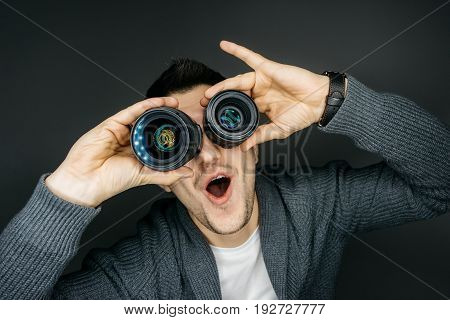 Portrait of a male photographer. He holds two lenses near the eyes. Funny facial expression