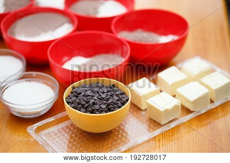 Cookery set of colorful bowls with chocolate drops flour cocoa powder sugar and blocks of butter stand at light brown wooden table. Shallow dof. Focus on chocolate.