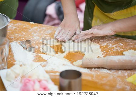 Cookery Scene With Female Hands Cutting Cookies From Raw Dough With Metal Cutter On Light Brown Tabl