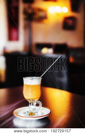 Cup of caramel coffee with straw on table (shallow dof)