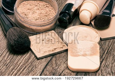 Makeup products for flawless complexion: foundation, concealer, powder with cosmetic sponge and professional make-up brushes. Shallow depth of field, toned image