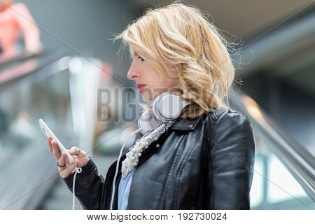 Woman listening to music and using her phone
