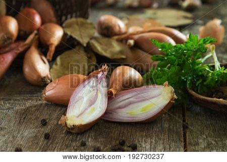 Whole and cut onions of shallot with green parsley close-up on a blurred background of scattered bulbs on a wooden background. Shallow depth of field.
