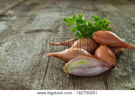 whole and sliced ​​onion shallot with green parsley closeup on a blurred wooden background. Shallow depth of field.