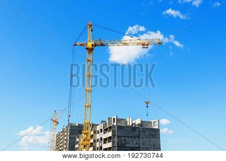 Tower crane on the construction site beneath blue cloudy sky