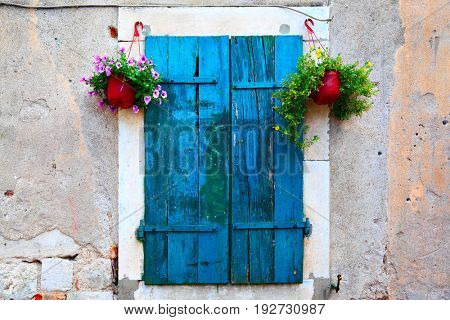 Old picturesque window with shutters and flowerpots
