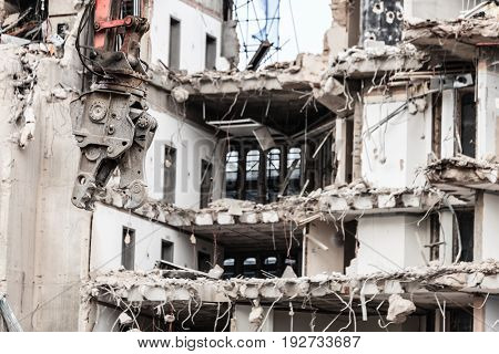 Urban scene. Dismantling of a house. Building demolition and crashing by machinery for new construction. Industry.