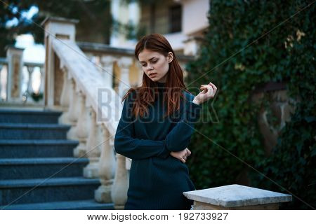 Red-haired woman standing in the street wearing a sweater, beautiful girl, architecture.