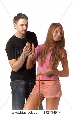 The young man offers delicious cake to the girl on a white background. Healthy food concept.