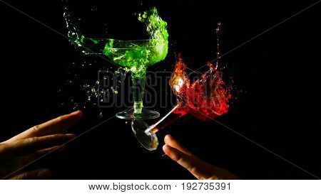 Clinking two glasses of red and green water in hand splash on dark background.