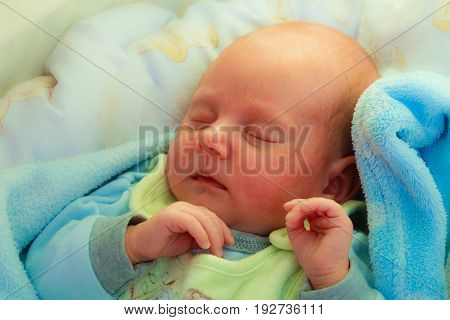 Little newborn baby in pyjamas lying on back and sleeping in bedding. Family parenthood childhood concept.