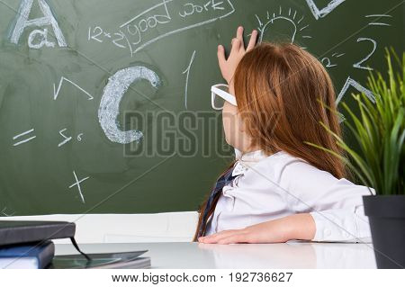 A classroom, a school, a board, a schoolgirl, a schoolgirl, a girl writing with chalk, studying.