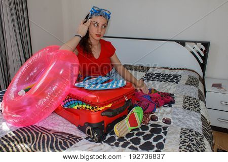 Young woman dreaming of a world trip sits near open suitcase on bed in hotel. Travel concept