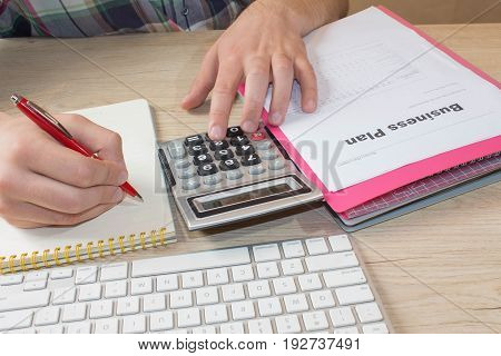 Close up Man hand using calculator and writing make note with calculate about cost at home office. Business concept. The Man and computer are using a calculator on the table in the office room