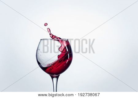 The one wine glass with red wine against white