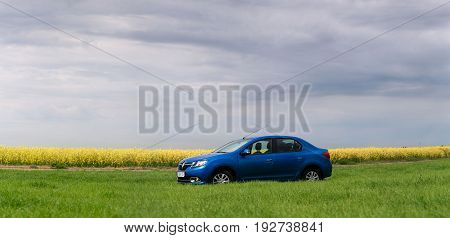 Gomel, Belarus - 24 May 2017: Reno Logan Blue Car Parked On A Rapeseed Field.