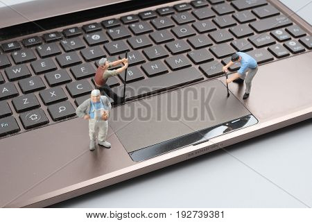 Mini Workmen Repairing A Laptop Key Board.