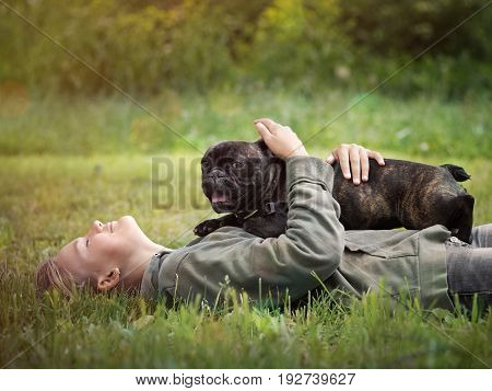 Girl lying in the grass hugging a dog. Nature green grass beautiful