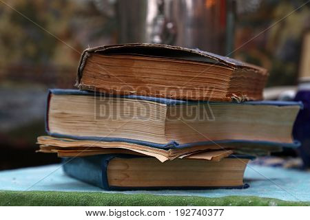 Stack of three old vintage aged and faded hardcover books and several booklets on table close up low angle view