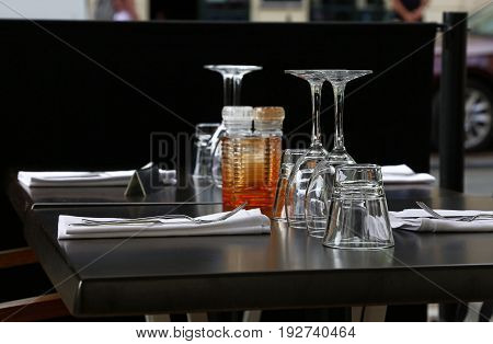 Restaurant table serving with water and wine glasses forks and knives utensils table napkins close up low angle side view