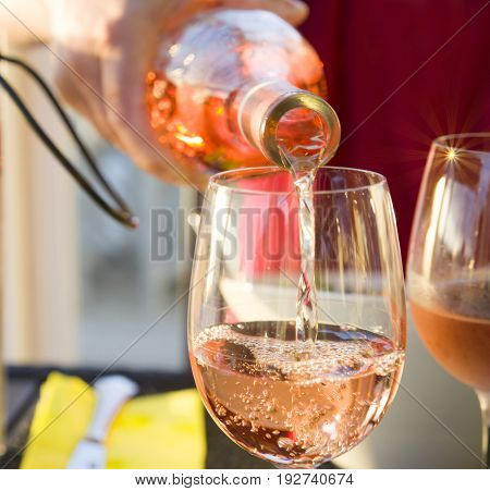The waiter pours the pink french wine into the glass