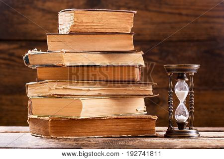 Stack Of Old Books And Retro Hourglass