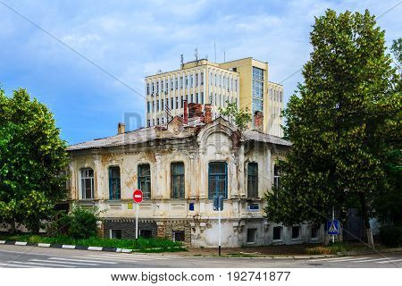 The old building of 1891 of construction in the started state against the background of the new high-rise modern well-groomed building. City of Armavir Krasnodar Krai.