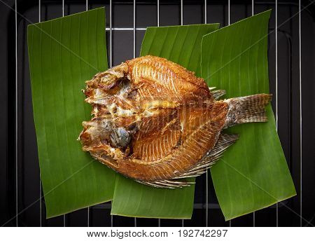 Fried tilapia fish on banana leaf in black metal tray Top view
