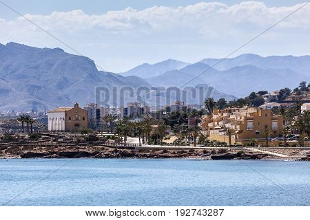 View of waterfront buildings and church in Isla Plana Puerto de Mazarron region of Murcia Spain