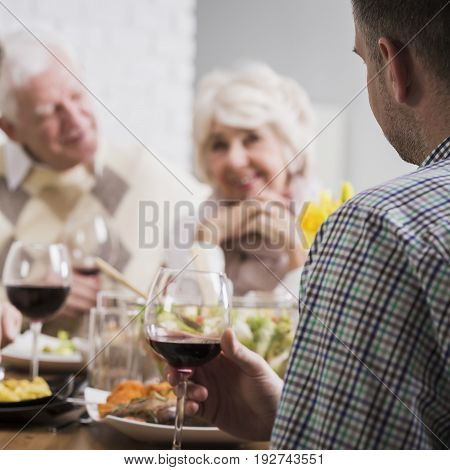 Mature couple and young marriage sitting beside table during family dinner