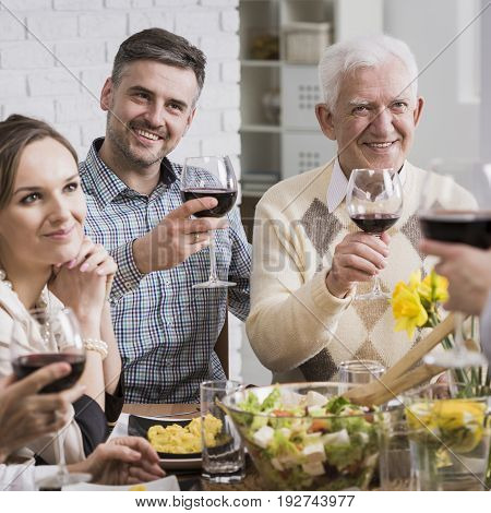 Happy family making a toast with red wine at the table during occasional meal
