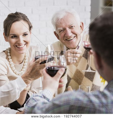 Happy mature couple and young pair toasting anniversary drinking red wine