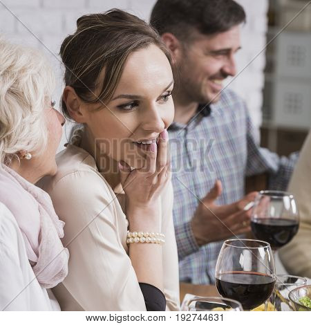 Mature woman whispering to young woman sitting beside table during family dinner
