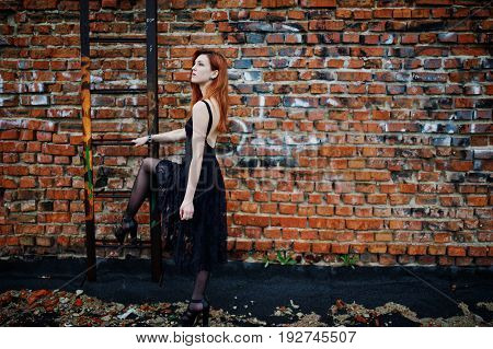 Red Haired Punk Girl Wear On Black Dress At The Roof Against Brick Wall With Iron Ladder.