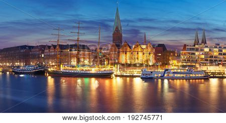 Embankment of the Weser River and Protestant Lutheran Saint Martin Church in the old town of Bremen, Germany. Night panoramic view.