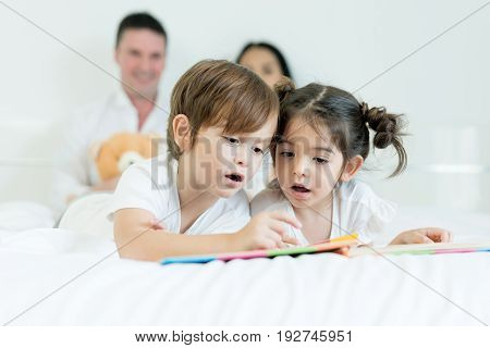 Asian brothers and Asian daughter reading book together on bed in bedroom with father and mother in background. Happy family concept.