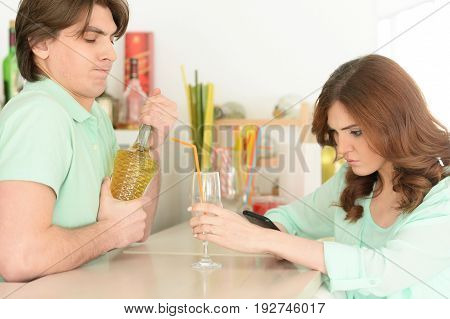 Young woman waiting for drink while young man opening bottle