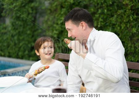 Father with little bcute boy eating barbecue in family lunch time at home.