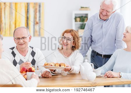 Pretty older woman serving a cake to her senior friends