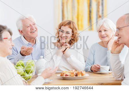 Friendly meeting of happy senior people in nursing home