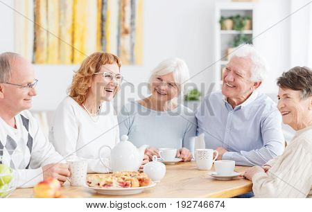 Group of happy older people on a meeting in senior club