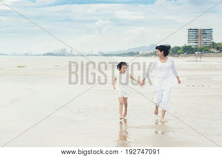 Happy Asian family mother and child daughter run laugh and play at beach. Happy family summer vacation concept.