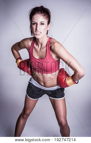 Angry beautiful athletic female boxer