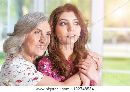 Portrait of a senor woman hugging her daughter