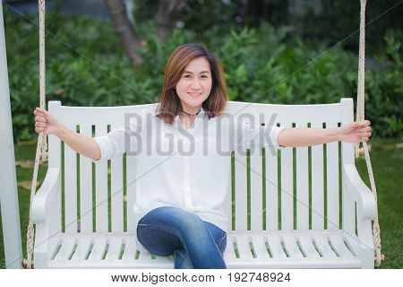 Single Asian Women Adult Relax Sitting At Swing Bench In The Park. Enjoy Healthy Good Life Concept.