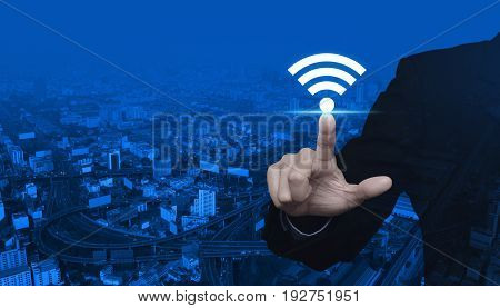 Businessman pointing to wi-fi button over modern city tower street and expressway Technology and internet concept