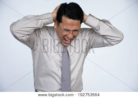 Feeling exhausted. Frustrated young man in formalwear touching his head with hands while standing against grey background